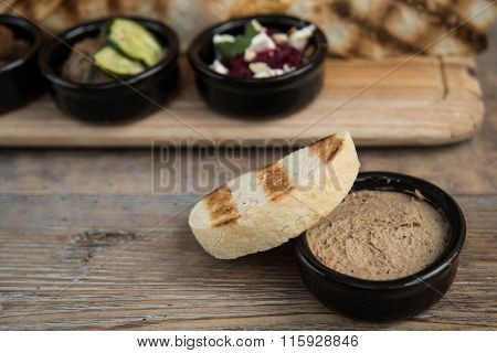Appetizers in small bowls are on the table, and next is the bread or pita bread