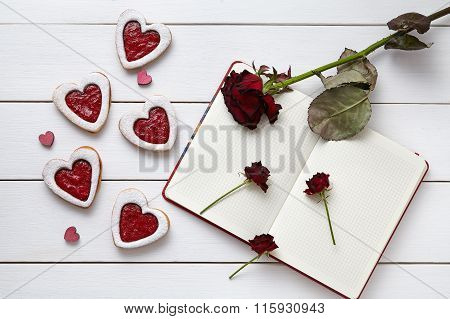 Heart shaped cookies with empty notebook and roses on white wooden background for Valentines day.