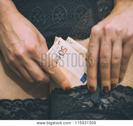 Prostitute hiding money in her stockings. Close-up view.