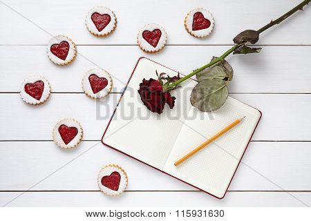 Shortbread homemade heart shaped cookies with empty notebook, pencil and rose flower on white wooden