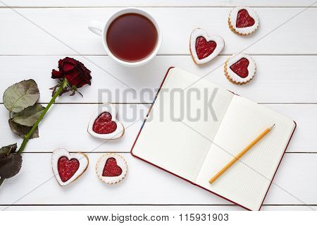 Shortbread heart shaped cookies with empty notebook, pencil, cup of tea and rose flower on white woo