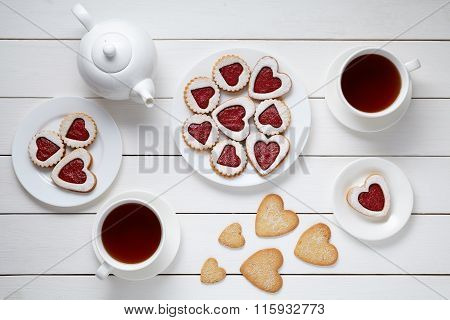 Heart shaped cookies for Valentines day with teapot and two cups of tea on white wooden background.