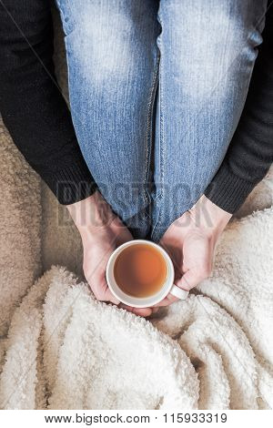 Hands Holding Cup Of Tea, Top View