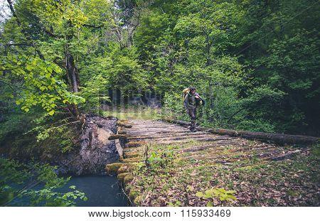 Man Traveler hiking on wooden bridge over river