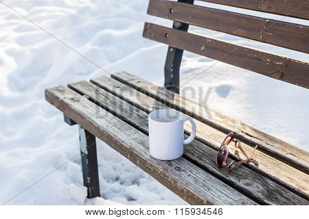 Single Cup Of Tea On Bench In Winter Park