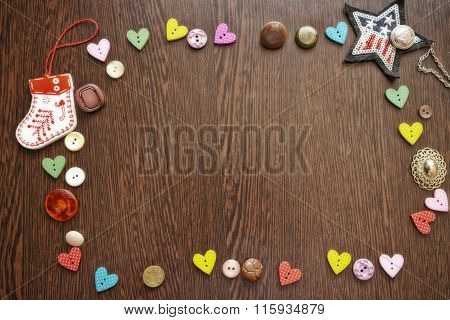 Buttons And Decorative Items Laid Out On Wooden Table In Form Of Frame