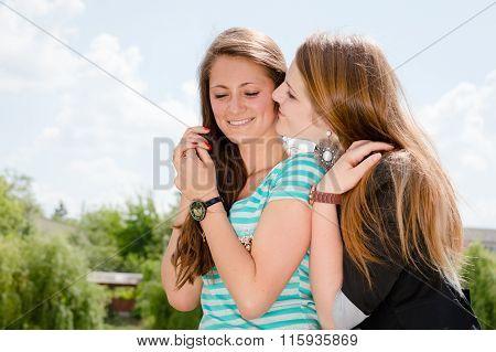 Two smiling girls whispering gossip