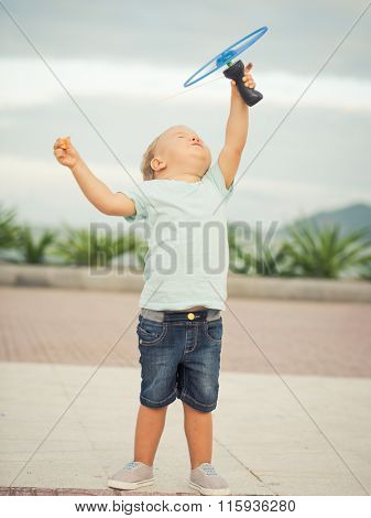 Boy with flying saucer outdoor. Leisure activity