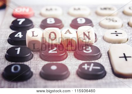 Calculator with the word loan written in wooden block letters
