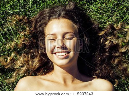 young cute summer girl on green grass outside relaxing smiling close up