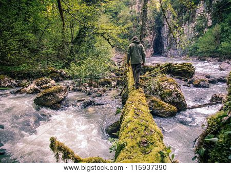 Man Traveler crossing river on log outdoor Lifestyle Travel