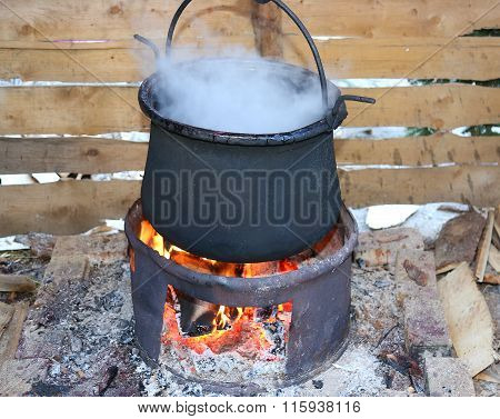Big Black Pot With The Fire Lit