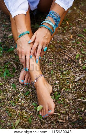 woman hands on barefoot feet with lot of bracelets in turquoise color sit on ground from above shot