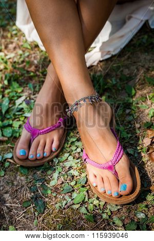 summer leather flip flops and ankle bracelet, outdoor shot from above on grass, shallow depth of field