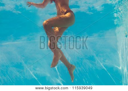 woman legs under water through the glass of the pool