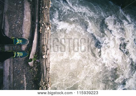 Woman Feet standing on wooden bridge edge over river