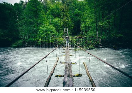 Man Traveler hiking on wooden bridge over river Travel