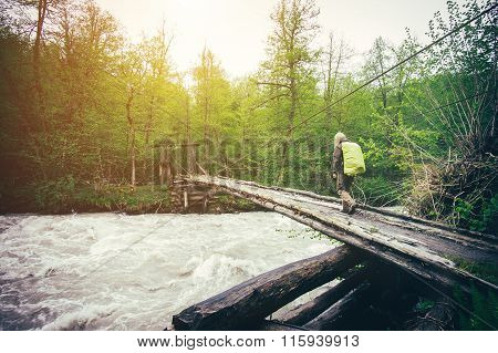 Woman Traveler with backpack hiking on bridge over river