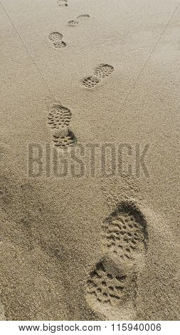 Human Footprints On The Beach Sand Leading Away From The Viewer