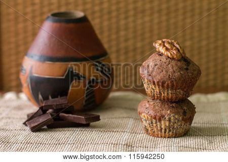 Bicolor muffin with chocolate, poppies and walnuts on paper and gourd with yerba mate.