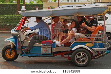 people are riding in tuk-tuk