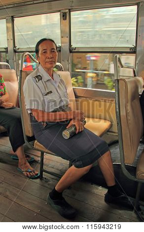 woman-conductor in bus is sitting on a seat
