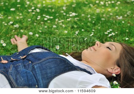Young Woman Lying In Grass With Flowers