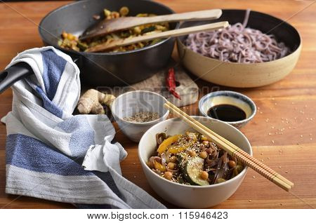 Black Rice Noodles And Stir Fried Vegetables In A Bowl, With Soy Sauce And Sesame Seeds