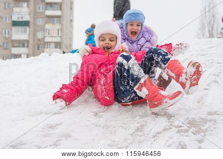 Two Happy Girls Slide Down The Icy Hill