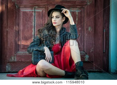Young beautiful brunette woman with red short dress and black hat posing sensual in vintage scenery.