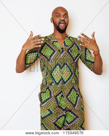 portrait of young handsome african man wearing bright green national costume smiling gesturing