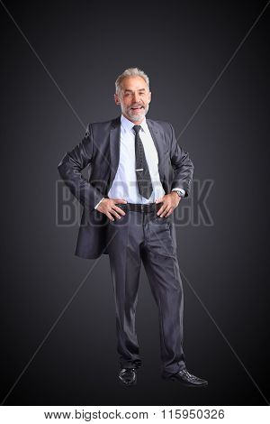 Confident Businessman Holding Hands On His Belt, Isolated On A Dark Background.