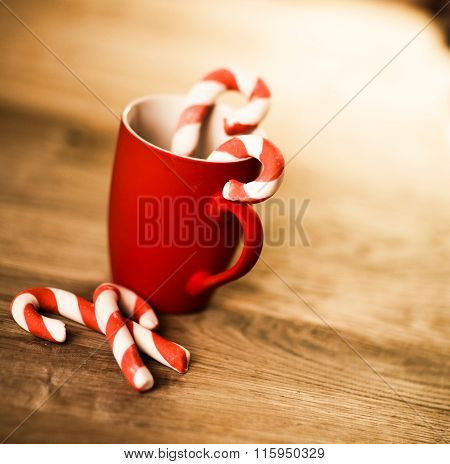 Mug Of Tea Or Coffee. Sweets. Christmas Decorations. Red Balls And Bells. Wooden Background.