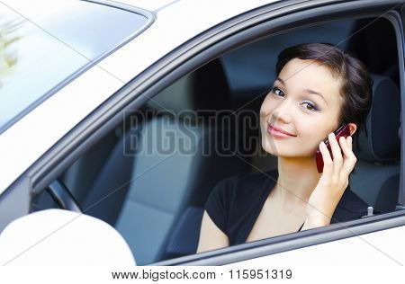 Woman sitting in a car and talking by mobile telephone