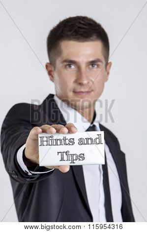Hints And Tips - Young Businessman Holding A White Card With Text