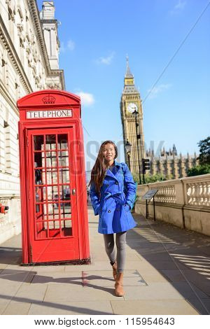 London tourism. Asian tourist woman walking by famous touristic attraction red phone booth or telephone box with Big Ben Westminster bridge in the background. Early spring or fall autumn travel.