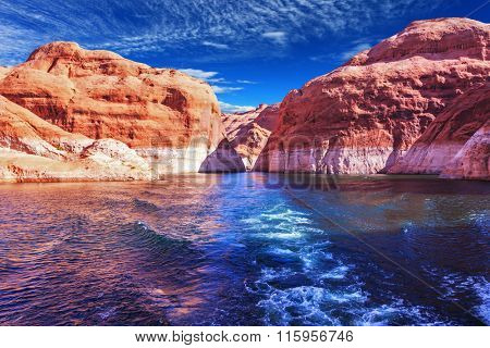 Walk on the tourist boat. Foam boat trail crosses the emerald waters. Red sandstone hills surround the lake. Lake Powell on the Colorado River