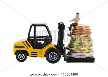 Soft focus of a miniature man sitting on a pile of Euro coins on a forklift truck, isolated on white