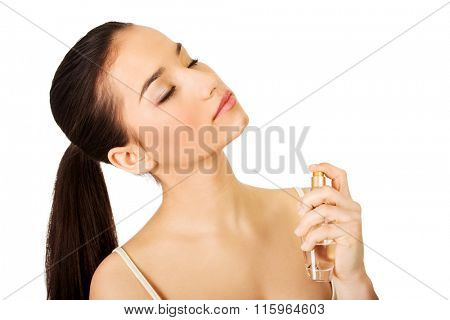 Young woman applying parfume.