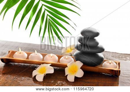 Spa stones with candles, plumeria and bamboo, isolated on white
