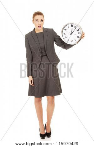 Shocked businesswoman with a clock.