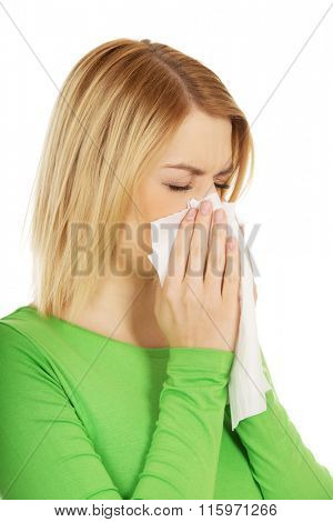 Woman sneezing to tissue.