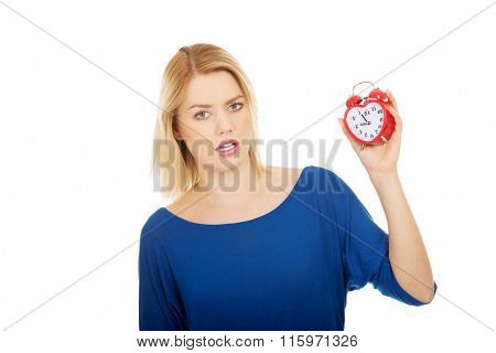 Shocked woman holding a clock.