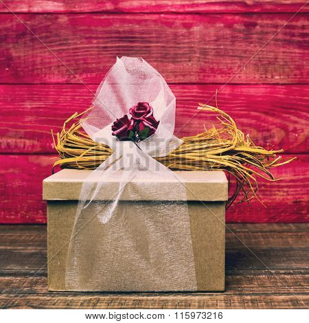 closeup of a gift box ornamented with flowers, natural fibers and tulle on a dark wooden surface, against a red rustic wooden background
