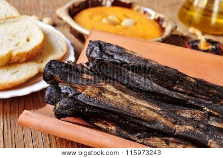 closeup of some barbecued calcots, sweet onions, served in a tile and a bowl with romesco sauce, typical of Catalonia, Spain