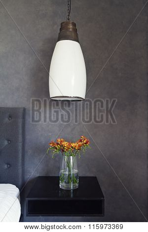 Close Up Of Pendant Light And Flowers On Bed Side Table