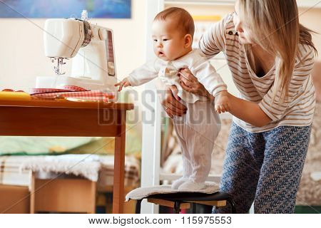 Mother and infant, home, the baby first steps, natural light. Child care combined with work at home.