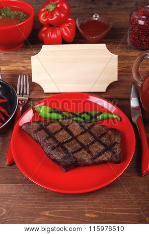 red theme lunch : fresh grilled bbq roast beef steak red plate green chili tomato soup ketchup sauce paprika glass ground pepper american peppercorn modern cutlery served wooden table empty nameplate