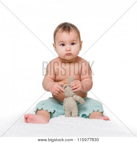 cute toddler sitting on a rug with toy and looking at camera isolated on white background