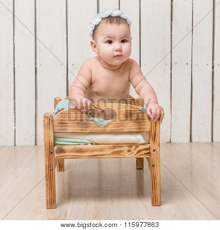 playful little child with hat sitting on a cot